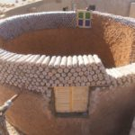 Jovem refugiado constrói moradias resistentes com garrafas de plástico
